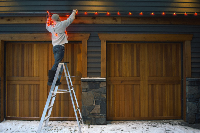 Man decorating house with Christmas lights --- Image by © Beau Lark/Corbis